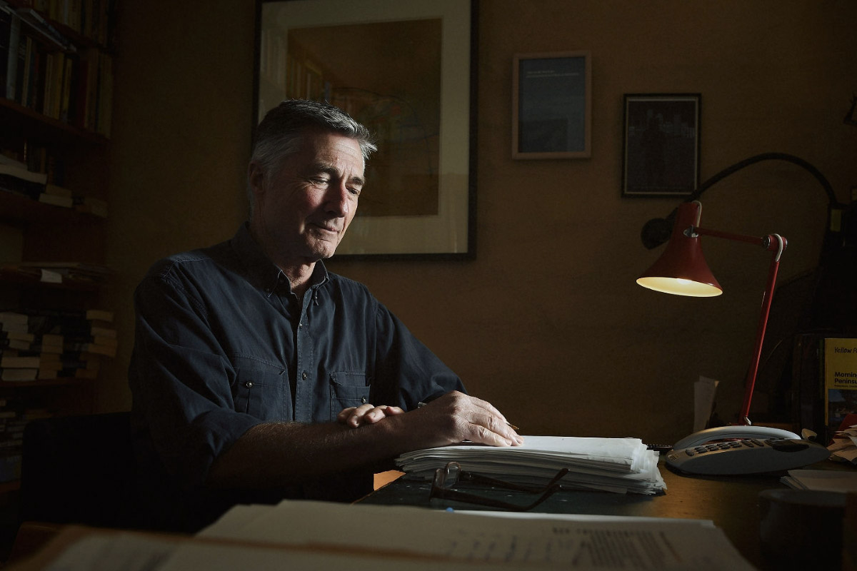 Photo of Garry at his writing desk in mood light with lamp and bookshelf in the background.