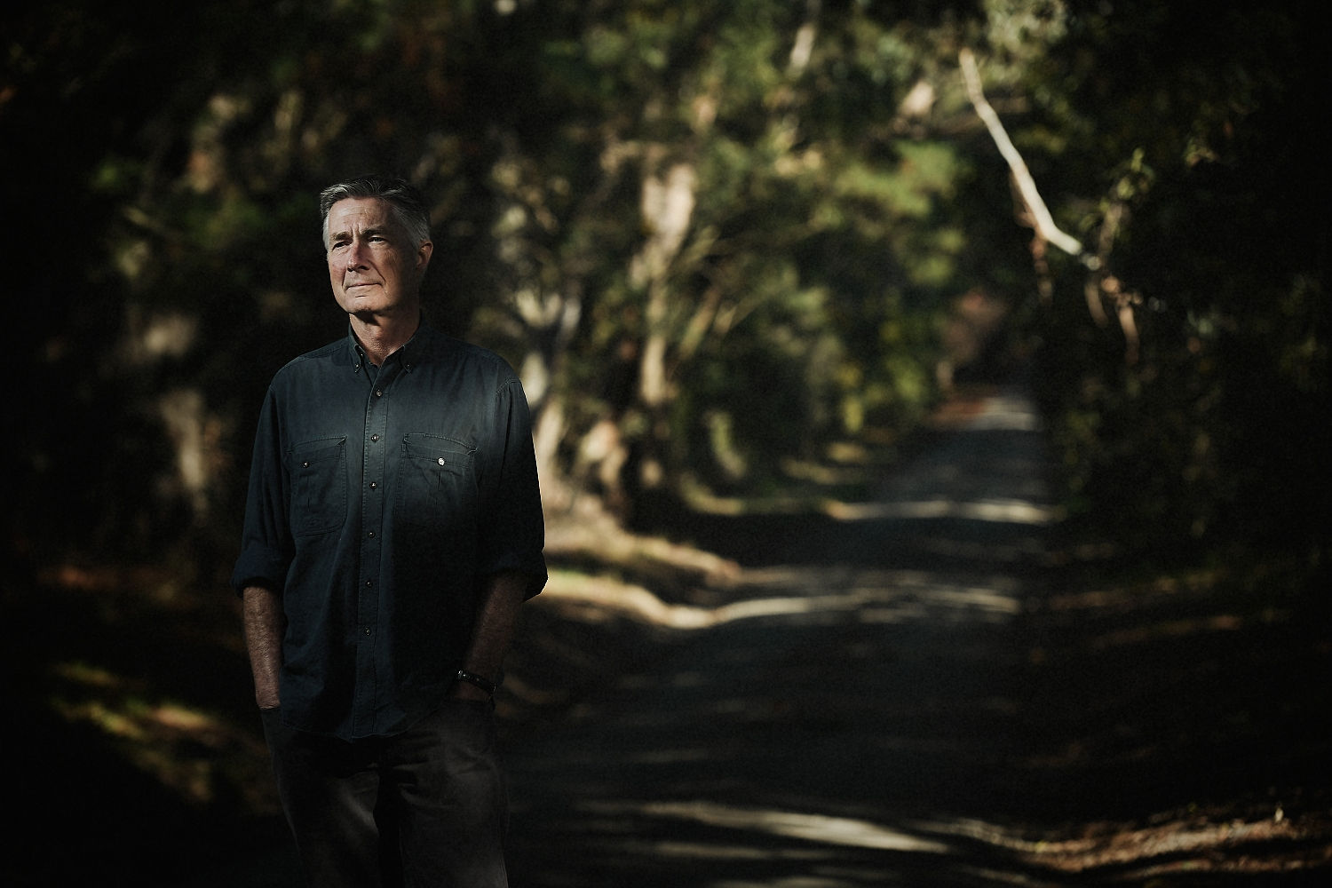 Photo of Garry looking pensive standing in the shadows of a long tree-lined driveway